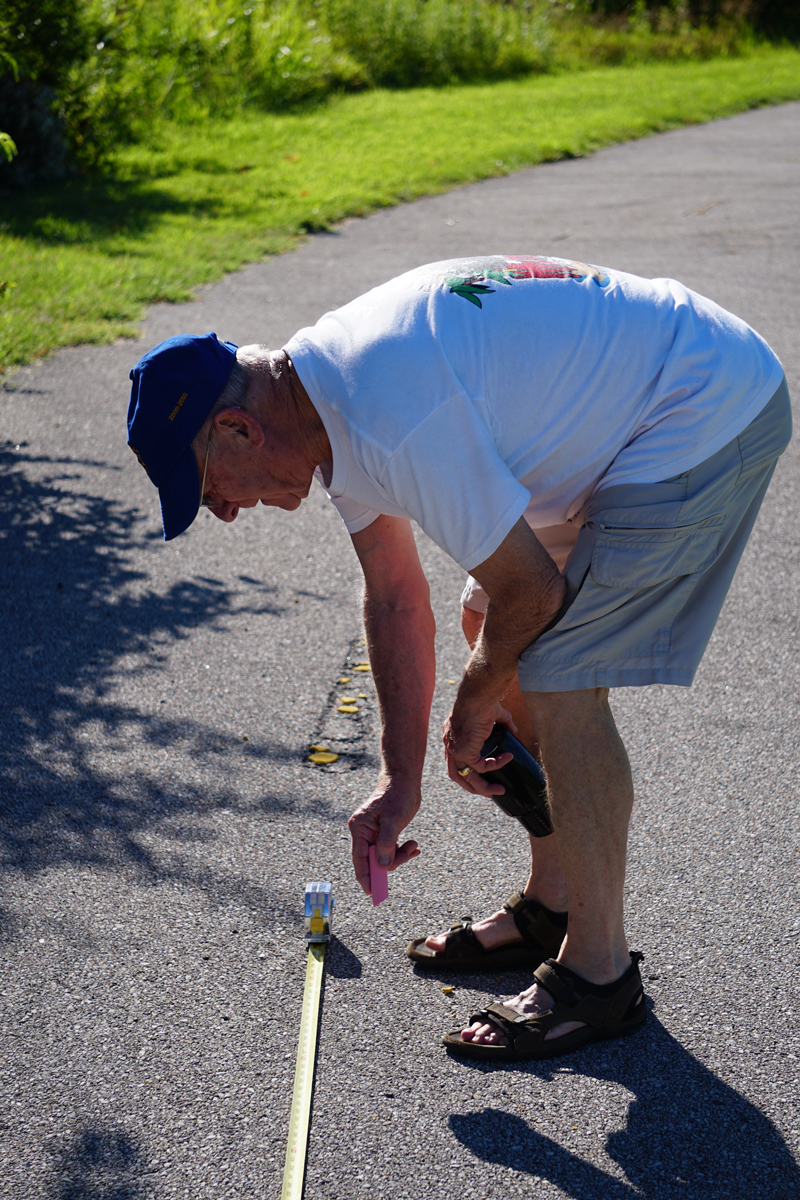 Larry Thompson makes careful measurements to assure the strips are three meters apart.