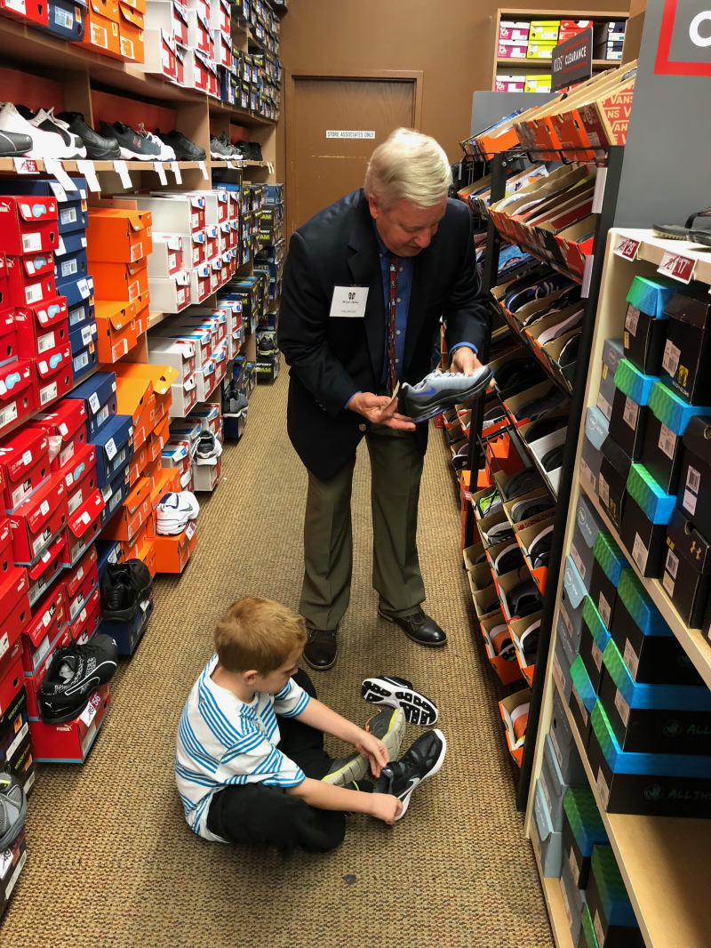 John assists student with shoes